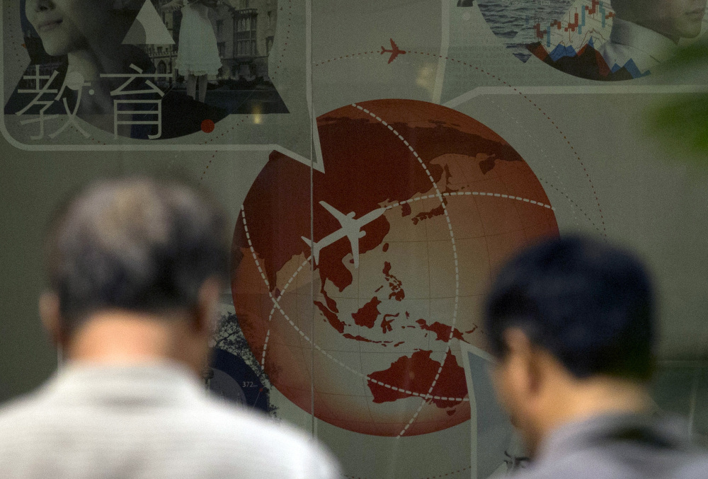 Relatives of Chinese passengers onboard the Malaysia Airlines flight MH370 walk past an advertisement for a bank depicting a plane flying over Asia at a hotel in Beijing Thursday, April 3, 2014. No trace of the Boeing 777 has been found nearly a month after it vanished in the early hours of March 8 on a flight from Kuala Lumpur to Beijing with 239 people on board.