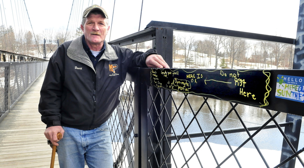OFFENDED: David Nevedomsky, of Winslow, leans on a graffiti-covered railing on the Waterville side of the Two Cent Bridge on Thursday. Nevedomsky said he is offended by the vandalism on the historic footbridge, and Thursday cleaned human excrement off it after municipal officials didn't respond to his complaints.