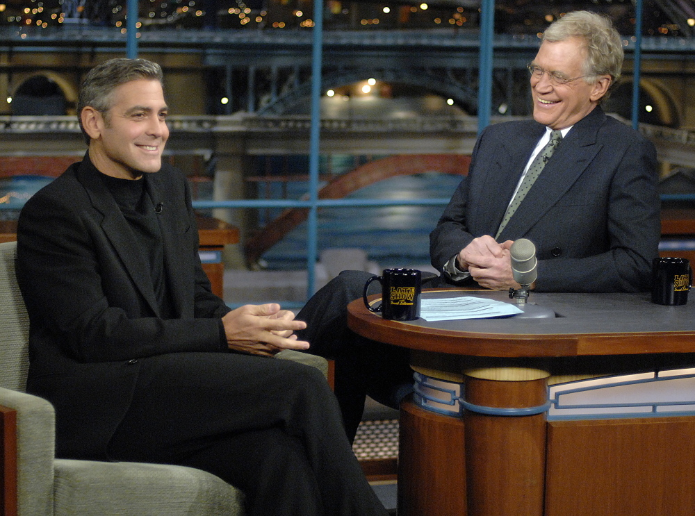 """In this photo released by CBS, George Clooney, left, laughs with host David Letterman on the set of """"The Late Show with David Letterman,"""" Tuesday, Nov. 28, 2006."""