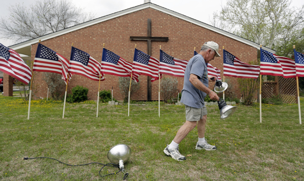 Bob Gordon works on a memorial for the victims of Wednesday's shooting at Fort Hood, Thursday, April 3, 2014, at Central Christian Church in Killeen, Texas. A soldier opened fire Wednesday on fellow service members at the Fort Hood military base, killing three people and wounding 16 before committing suicide.