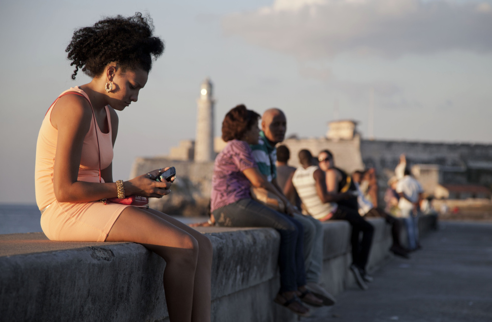"""A woman uses her cellphone as she sits on the Malecon in Havana, Cuba, recently. The U.S. Agency for International Development masterminded the creation of a """"Cuban Twitter,"""" a communications network designed to undermine the communist government in Cuba, built with secret shell companies and financed through foreign banks."""