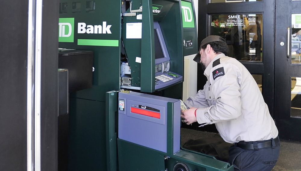 A guard from Loomis fills the ATM that a homeless man withdrew about $37,000 from Friday at the TD Bank on Maine Mall Road in South Portland.