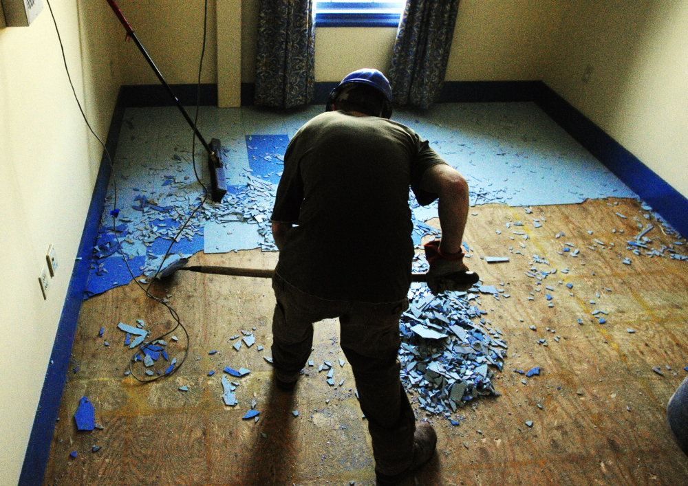 NEW TENANTS: MacKenzie Dunton, of Peachey Builders, chips tiles off the floor in the Haynes Building at the corner of St. Catherine and East Chestnut Streets, left, just up hill from the old MaineGeneral Medical Center on Friday in Augusta.
