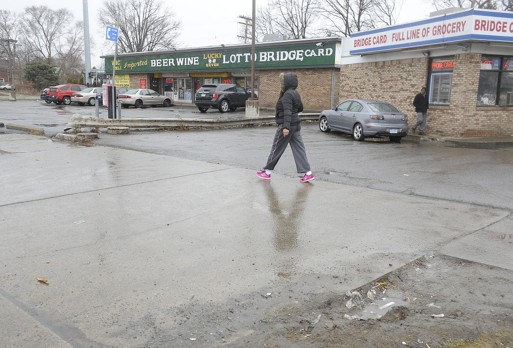 A pedestrian passes by the scene of an attack on Wednesday in Detroit.