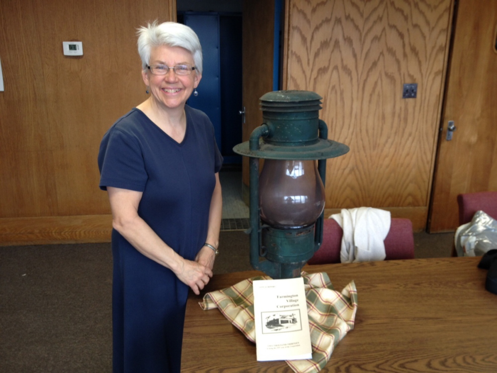 LIGHT: Jane Woodman, business manager for the Farmington Village Corporation, stands next to a 130-year-old lamp that came from an era when the corporation, not the town, ran the municipal streetlights.
