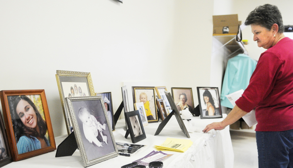 Staff photo by Andy Molloy Mary Wakefield examines photos of homicide victims Sunday during the annual luncheon of the Maine chapter of Parents of Murdered Children in Augusta. At left is a portrait of Brooke Locke, who was 21 whe she murdered in November 2013 at a Bangor apartment that she shared with the alleged killer. Wakefield of Waterville is the mother of Rhonda Wakefield, who was murdered by her estranged husband in 2007 in Fairfield.