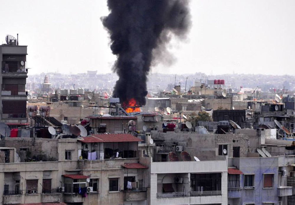 Smoke and flames rise from a building that was attacked by a mortar shells in Damascus, Syria, on Saturday.