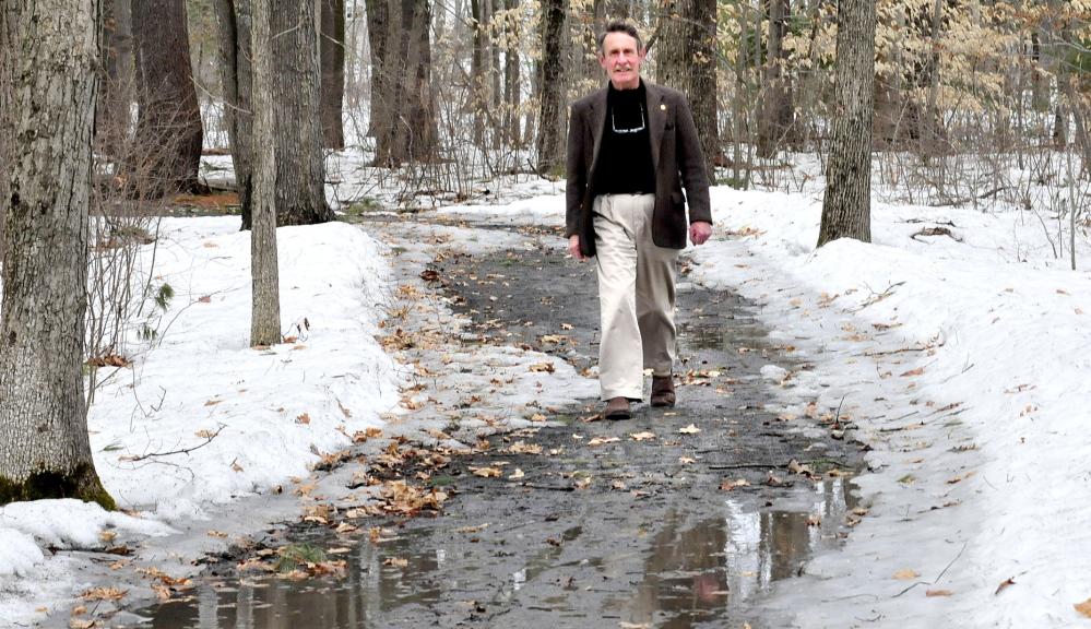 LONG TREK: Peter Garrett, president of Kennebec Messalonskee Trails, walks along the Winslow Community Trail on Monday. Garrett is retiring from the organization.