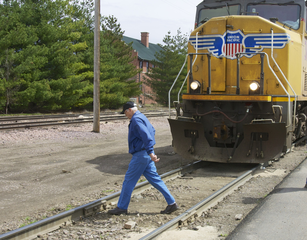 In this photo taken on April 7, 2010, a man crosses a railroad track in front of a stationary locomotive in Fremont, Neb. Regulators and the railroad industry are launching a new campaign Tuesday.