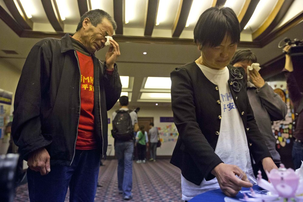 Feng Zhishang, left, cries near Xie Xincui as they mark the birthday of their son Feng Dong, a passenger on board the Malaysia Airlines Flight 370, at a hotel where relatives gather to wait for news of the missing plane in Beijing, China, on Tuesday.