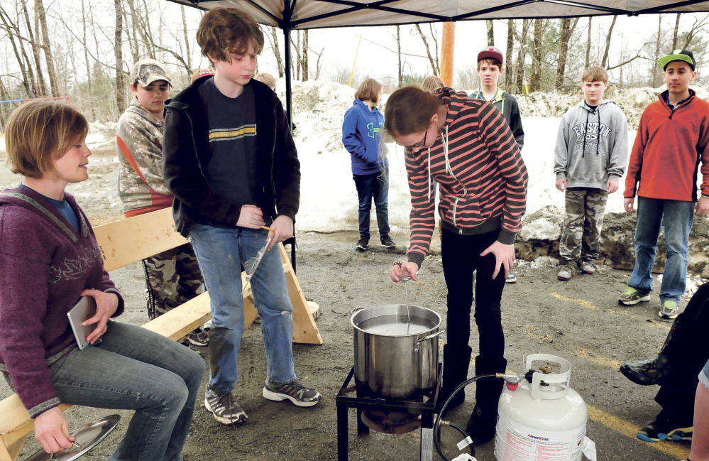BOILING FAD: Cornville Regional Charter School student Grace Jewell takes a temperature reading of boiling maple sap Tuesday as Malcolm Harmon records the progress under direction of teacher Johanna Burdet, left.