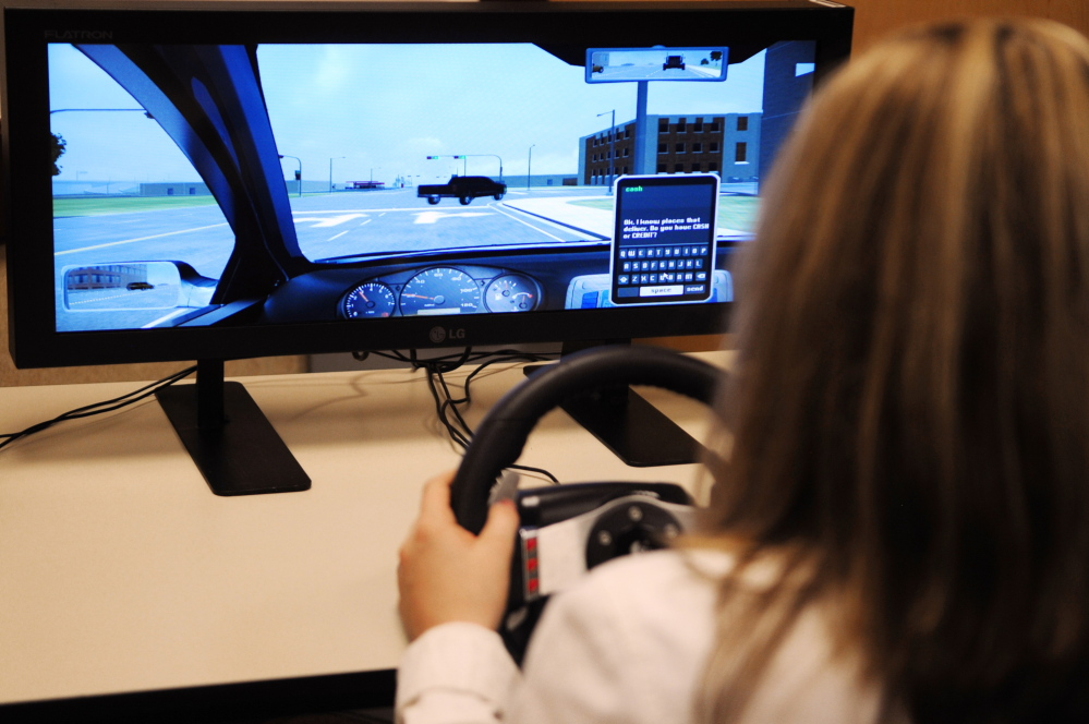 distracted driving test: Winthrop High School freshman Kayleigh Oberg demonstrates a driving simulator after a news conference about distracted driving on Thursday in Augusta.