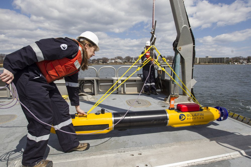 A submarine built by Bluefin Robotics is prepared by systems engineer Cheryl Mierzwa to be deployed into the water in Quincy, Mass., on Wednesday. Bluefin Robotics shipped a version of their submarine to help locate missing Malaysian Airlines Flight 370.