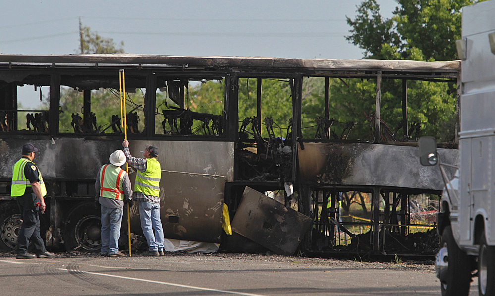 Investigators look over the charred remains of a tour bus Friday in Orland, Calif. At least 10 people were killed and dozens injured in the fiery crash on Interstate 5 .