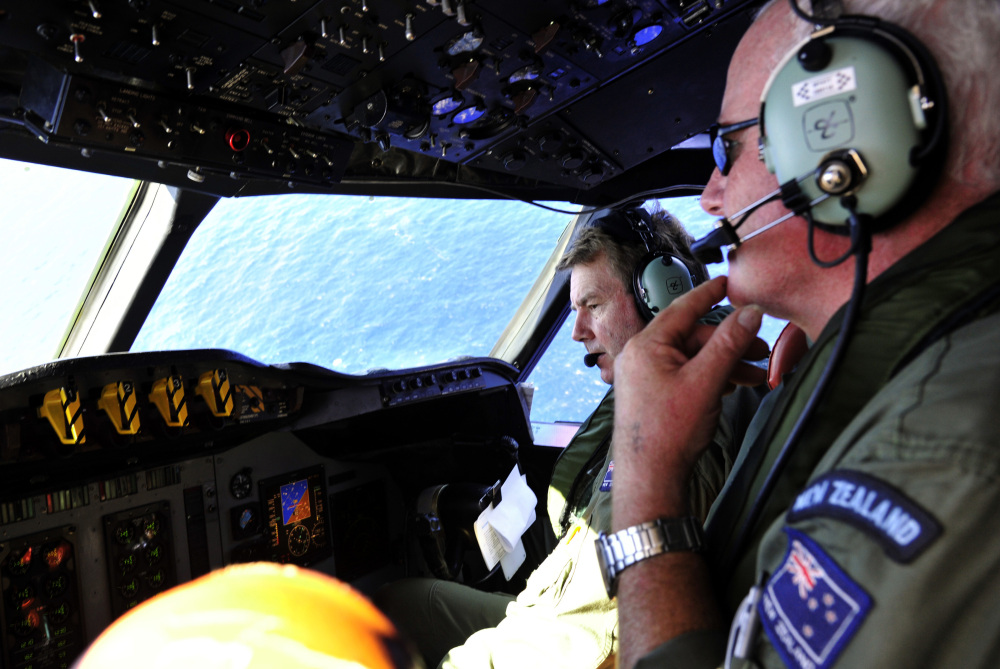 Royal New Zealand Air Force co-pilot squadron leader Brett McKenzie, left, and flight engineer Trent Wyatt sit in the cockpit aboard a P-3 Orion looking for the missing Malaysia Airlines Flight MH370 on Friday.