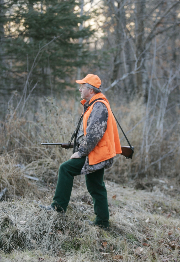 David Lowell scans the woods for deer on the tote road into Moose-Valley-Camp in western Maine. Hunters are seeing fewer deer in northern and western Maine, despite programs to cull predators and to plant food for deer.
