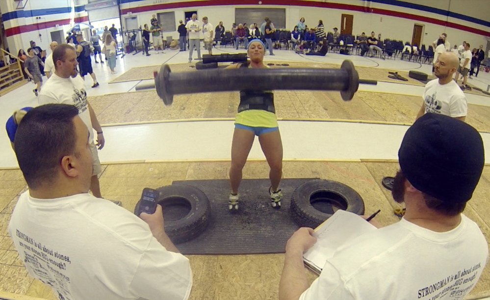Heavy Lifting: Judges watch as Hollie MacKenzie, of Oakland, competes the max log clean during the Central Maine Strongman 7 competition on Saturday at Augusta Armory. Increasingly heavier weights are added to the metal log each round until only one last competitor can the lift it.
