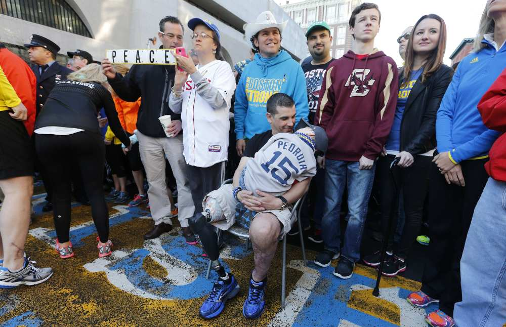 Boston Marathon bombing survivor Marc Fucarile, seated, talks to his son Gavin, 6, at the finish line of the Boston Marathon in Boston on Saturday. About 3,000 people, including survivors and first-responders showed up to participate in a Sports Illustrated photo shoot to commemorate the one-year anniversary of the bombings.