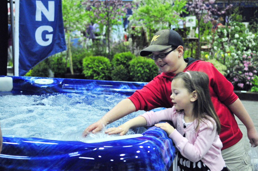 Just checking: Cooper Hall, top, and Olivia Hall test the warmth of water in a hot tub Saturday during the Manchester Lions Home and Garden Show at the Augusta Civic Center.