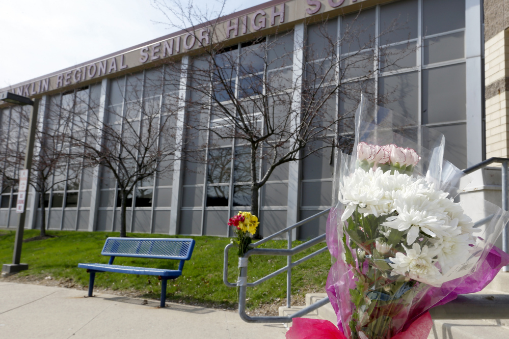 A bouquet of flowers is taped to a stairway rail near the closed entrance to Franklin Regional High School near Pittsburgh last week in Murrysville, Pa.