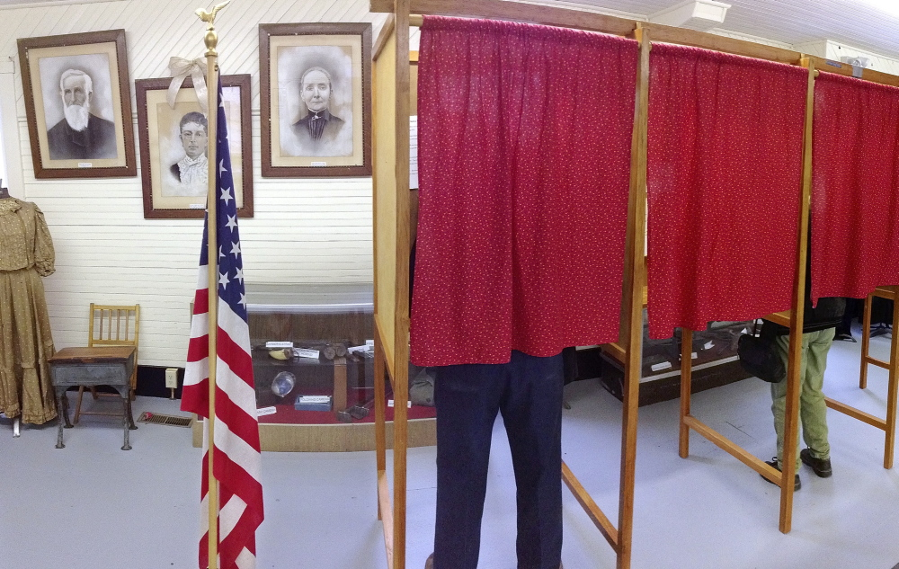 DECISION TIME: Voters cast ballots during a referendum Tuesday to decide whether the town will withdraw from Alternative Organizational Structure 97 at Starling Hall in Fayette. The building on Route 17 features displays set up by the Fayette Historical Society.
