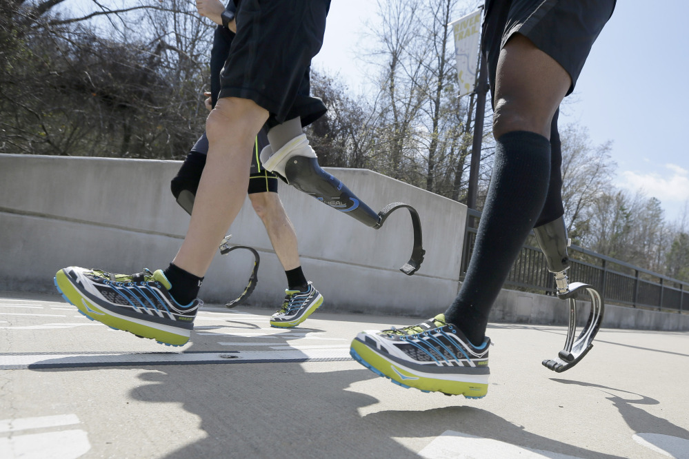 Amputee marathon runners Andre Slay, right, Chris Madison, back, and Jeff Glasbrenner train in Little Rock, Ark., this year, 4,781 runners are taking the Boston Marathon up on its offer to return – an opportunity to settle some unfinished business when they line up at the start again.