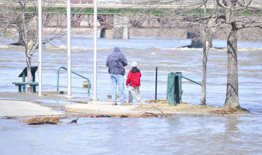 An adult and child watch the rising Kennebec River beside the Augusta Waterfront Park sign on Wednesday in downtown Augusta. The river was predicted to rise another few feet in the evening.