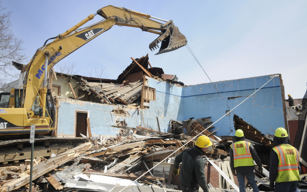 LAST GASP: McGee Construction workers pull down walls of the Masonic Lodge in Winthrop on Thursday.