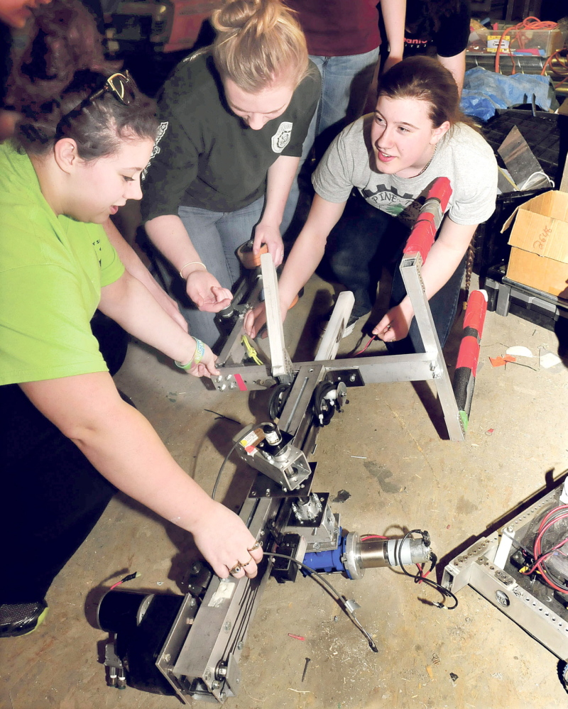REPAIR: Messalonskee High School robotics team members make repairs on the claw part of the team's robot, which will compete in the national championship in St. Louis, Mo. From left are Sydney O'Neal, Dakota Condon and Gretchen Rice.