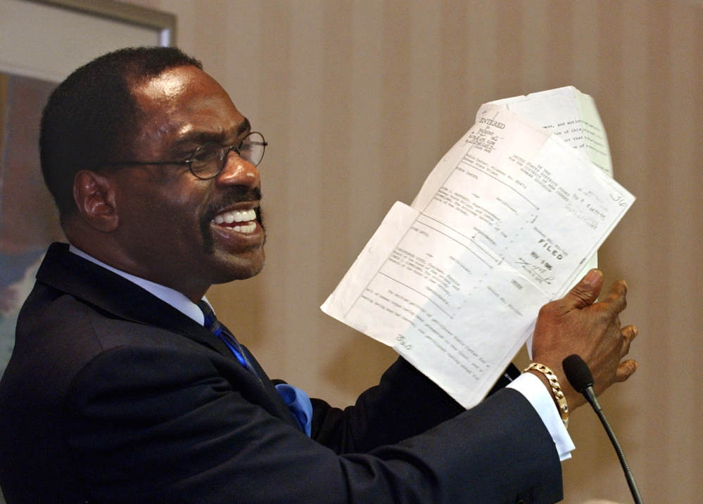 """Former boxer Rubin, """"Hurricane"""" Carter, holds up the writ of habeas corpus that freed him from prison, during a news conference held in Sacramento, Calif., in January 2004. Carter, who spent almost 20 years in jail after twice being convicted of a triple murder he denied committing, died at his home in Toronto on Sunday. He was 76."""