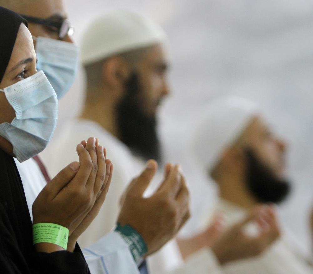 Muslim pilgrims, some wearing masks, pray near Mecca in Saudi Arabia in 2013.