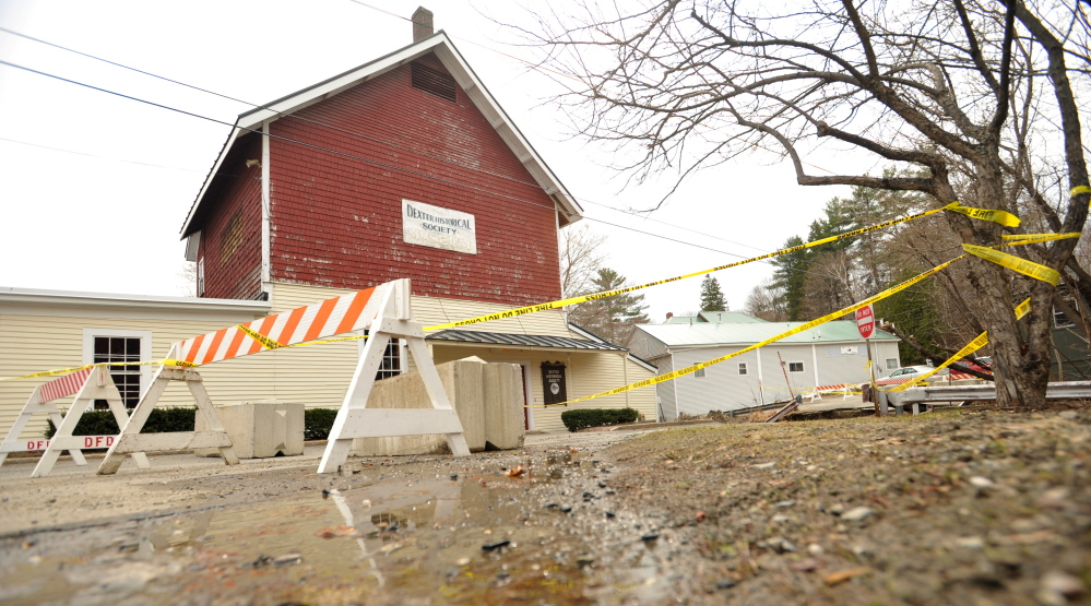 Staff photo by Michael G. Seaman LEFT HANGING: The Dexter Historical Society Grist Mill Museum remains in a precarious state Tuesday after flooding threatened the structure and washed out a road in Dexter last week.