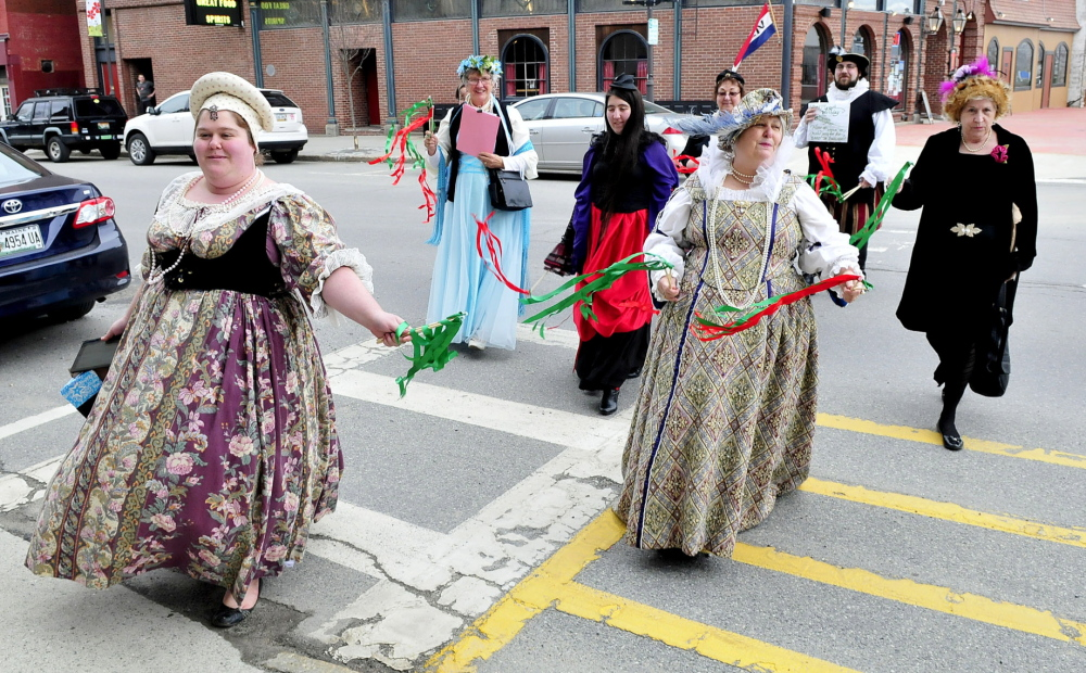 HAPPY BIRTHDAY: Dressed in period outfits a group from the Recycled Shakespeare company crosses Main Street in Waterville during a celebration Shakespeare's 450th birthday. Leading the group is Emily Fournier, left, and her mother, Lyn Rowden.