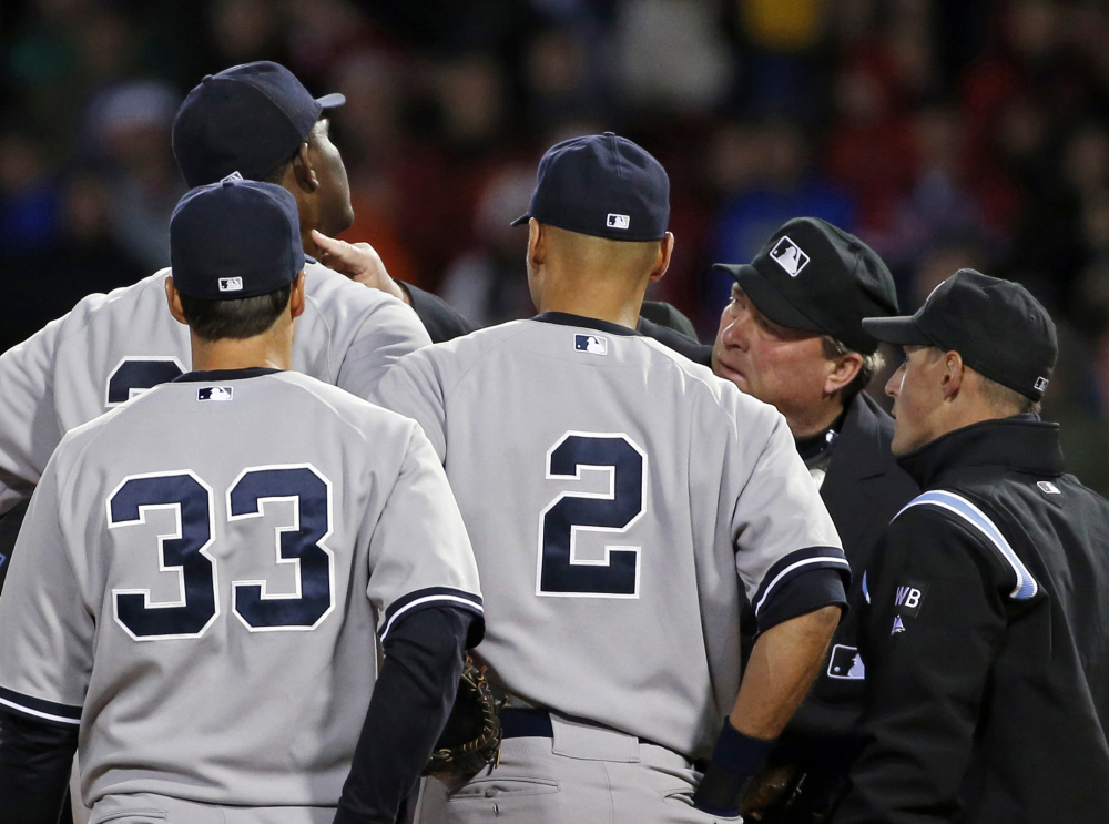 Home plate umpire Gerry Davis touches the neck of New York Yankees starting pitcher Michael Pineda in the second inning of Wednesday's game against the Boston Red Sox at Fenway Park in Boston. Pineda was ejected after umpires found a foreign substance on his neck.
