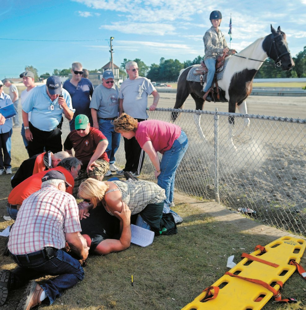 gate accident: People attend to the injured who were struck by the racing gate at the start of the 13th race at the WIndsor Fair in this September 2010 photo. The gate, towed by a vehicle, hit five people watching the race.
