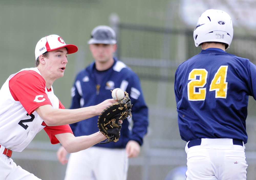 TOUGH HOLD: Cony High School's Mitchell Bonenfant can't hold onto a throw Wednesday while attempting to tag Mt. Blue's Amos Herrin at first base in Augusta. The Cougars beat the Rams 5-2.