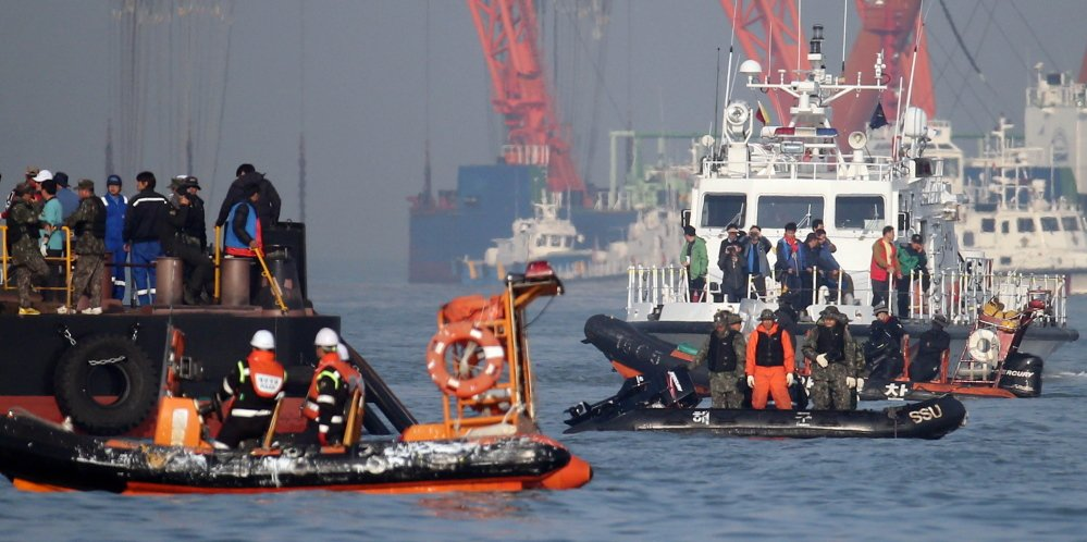 Searchers and divers look for people believed to have been trapped in the sunken ferry Sewol Wednesday. The victims of the April 16 disaster are overwhelmingly students of a single high school in Ansan, near Seoul. More than three-quarters of the 323 students are dead or missing, while nearly two-thirds of the other 153 people on board survived.