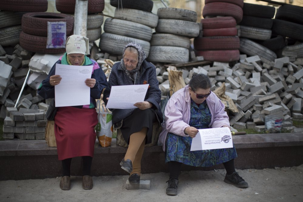 Women read a leaflet distributed by pro-Russian activists behind barricades near a regional administration building that was seized by pro-Russian activists earlier in Donetsk, Ukraine, on Wednesday.