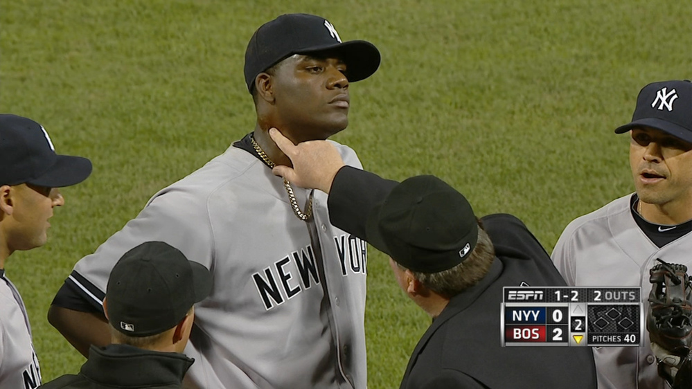 OOPS: Home plate umpire Gerry Davis touches the neck of New York Yankees starting pitcher Michael Pineda in the second inning Wednesday of the Yankees' game against the Boston Red Sox at Fenway Park in Boston. Pineda was ejected after umpires found a foreign substance on his neck.