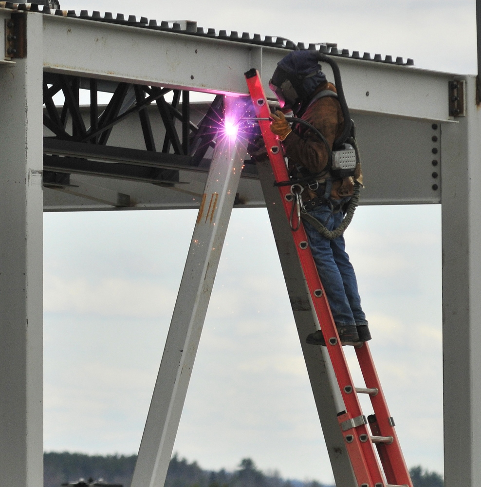 NEW DEVELOPMENT: A welder works on a new building Thursday at the Marketplace at Augusta that will be home to Chipotle Mexican Grill, Yankee Candle, Supercuts, Orange Leaf Frozen Yogurt, Elevation Burger and two other small retailers later this fall.