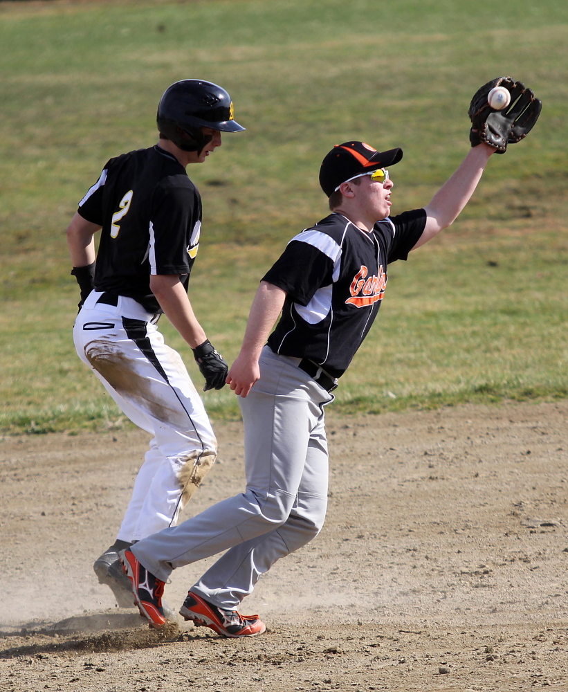 Safe: Gardiner Area High School's Josh Farrin tries to control a short hop from catcher Ian Moore as Marancook Community School's Nick LaCasse steals second base during first inning action in Gardiner on Friday. Maranacook won 11-10.