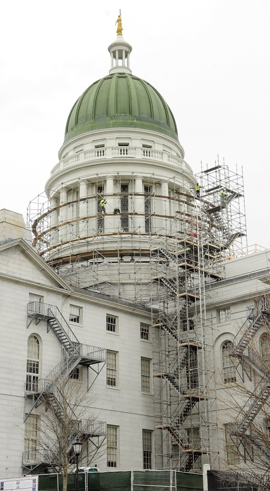 Rising Up: Workers build scaffolding around the State House dome on Wednesday in Augusta. This is the first part of a project to replace the old copper dome on the Capitol.