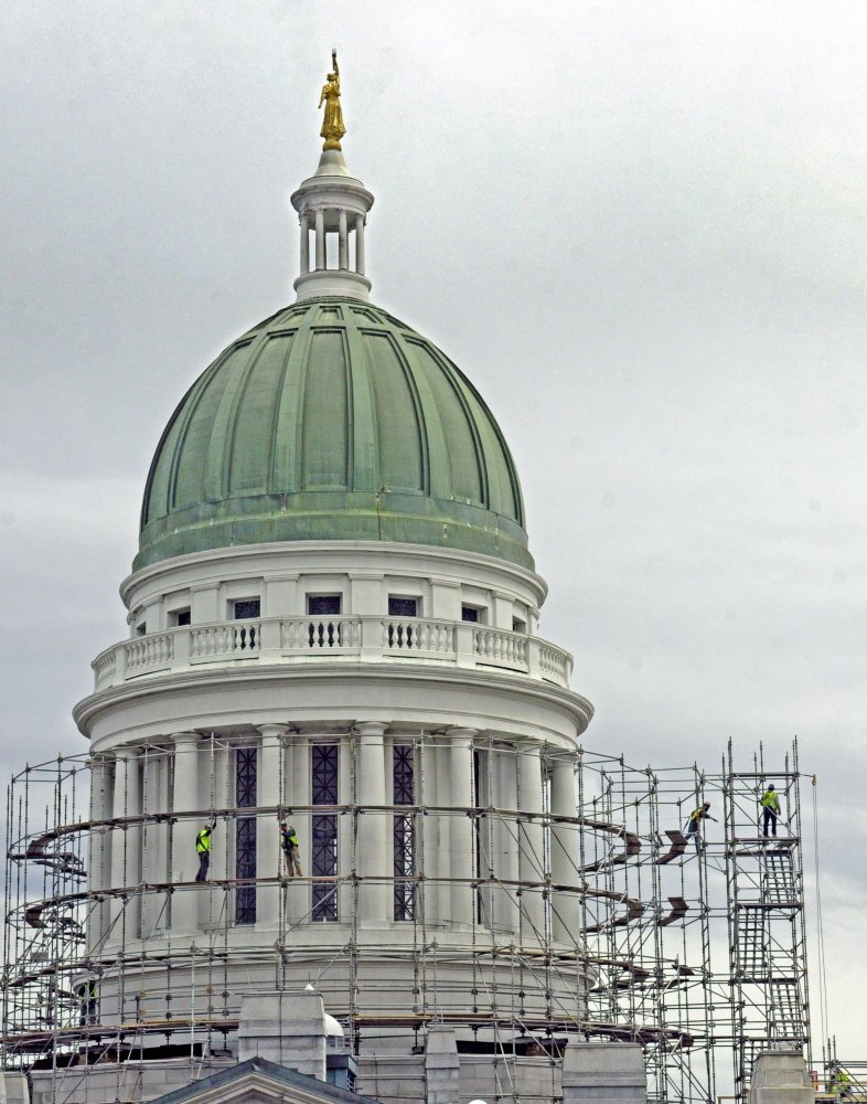 Out with the old: Workers build scaffolding around the State House dome on Wednesday in Augusta. This is the first part of a project to replace the old copper dome on the Capitol.