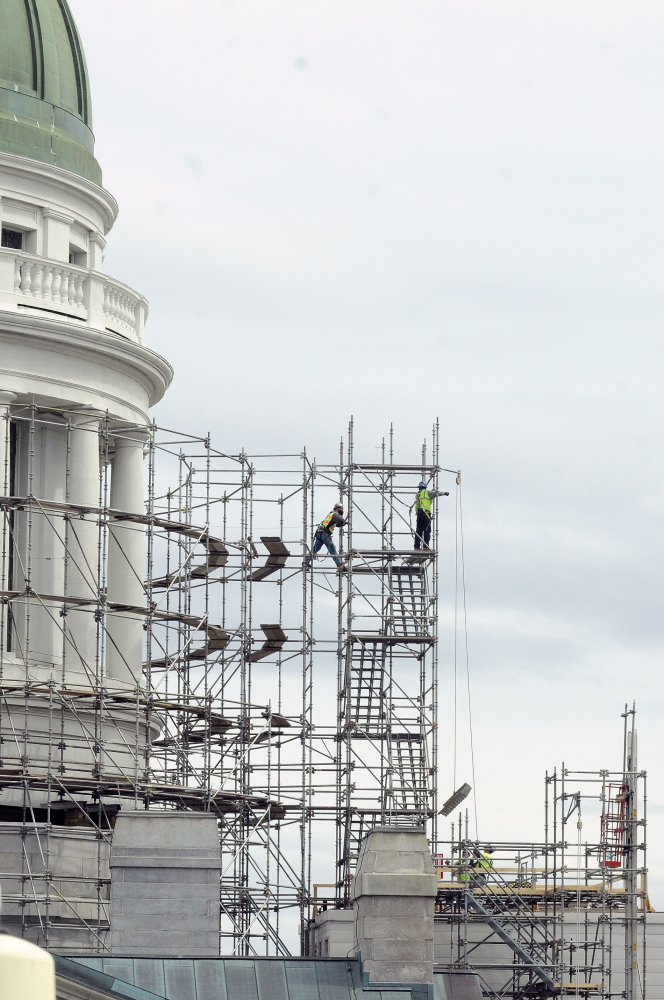 In with the New: Workers build scaffolding around the State House dome on Wednesday in Augusta. This is the first part of a project to replace the old copper dome on the Capitol.