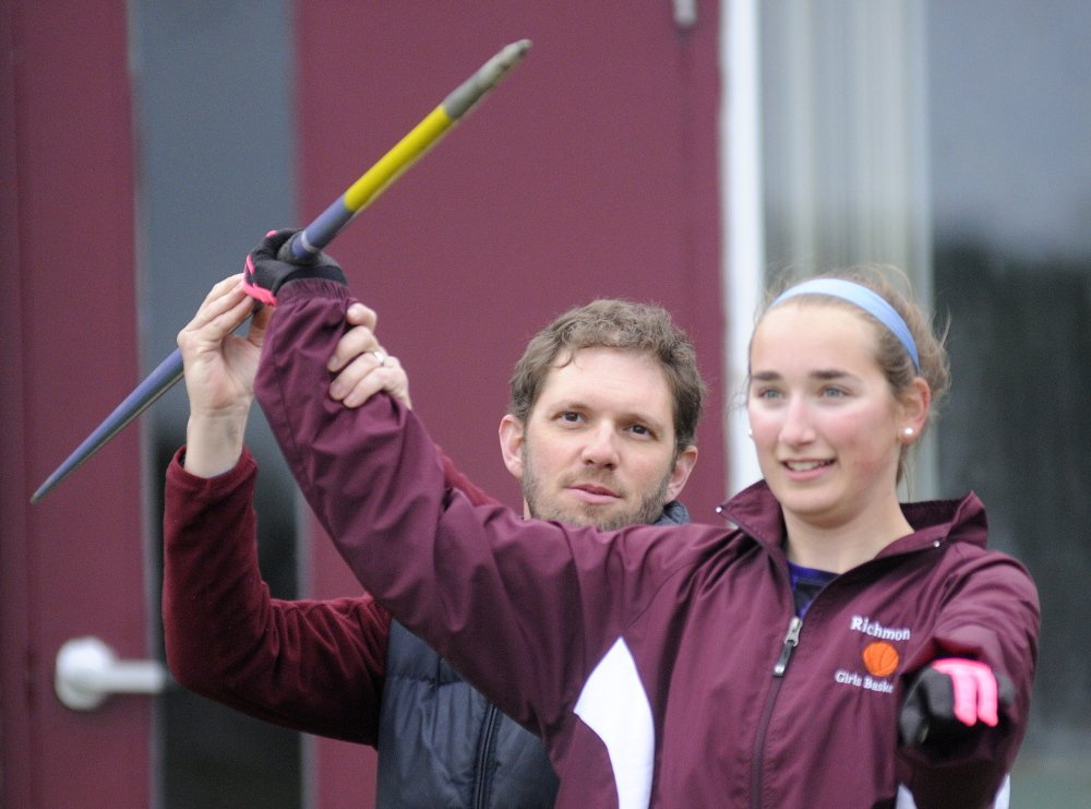 Staff photo by Andy Molloy Richmond Track and Field coach Dave Gagne shows Julie Plummer how to grip a javelin Monday outside the school.