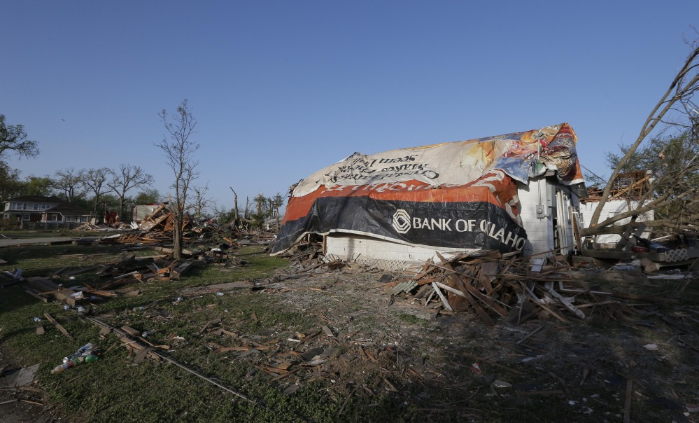 A tornado-damaged home is covered by tarps in Baxter Springs, Kan., Monday. The tornado left a trail of shattered homes, twisted metal and hanging power lines. One person died, but it was not clear whether the death was related to the storm.