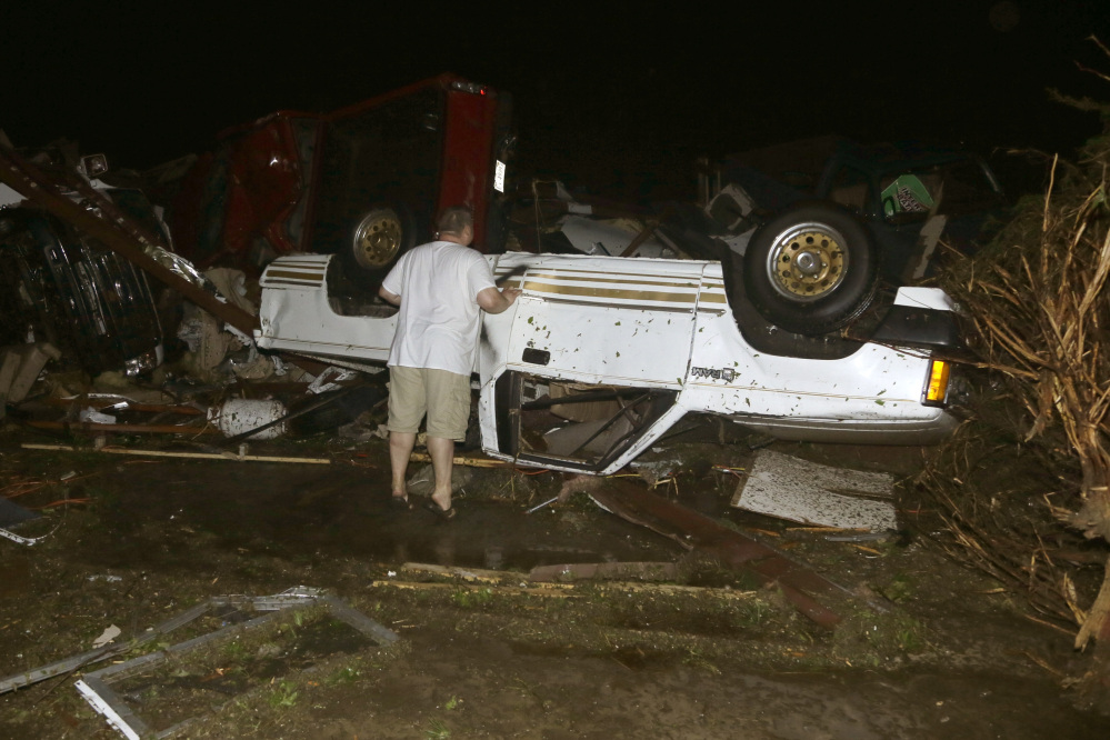 John Ward, an auto and RV dealer, looks at tornado damage to one of his trucks in Mayflower, Ark., Sunday.