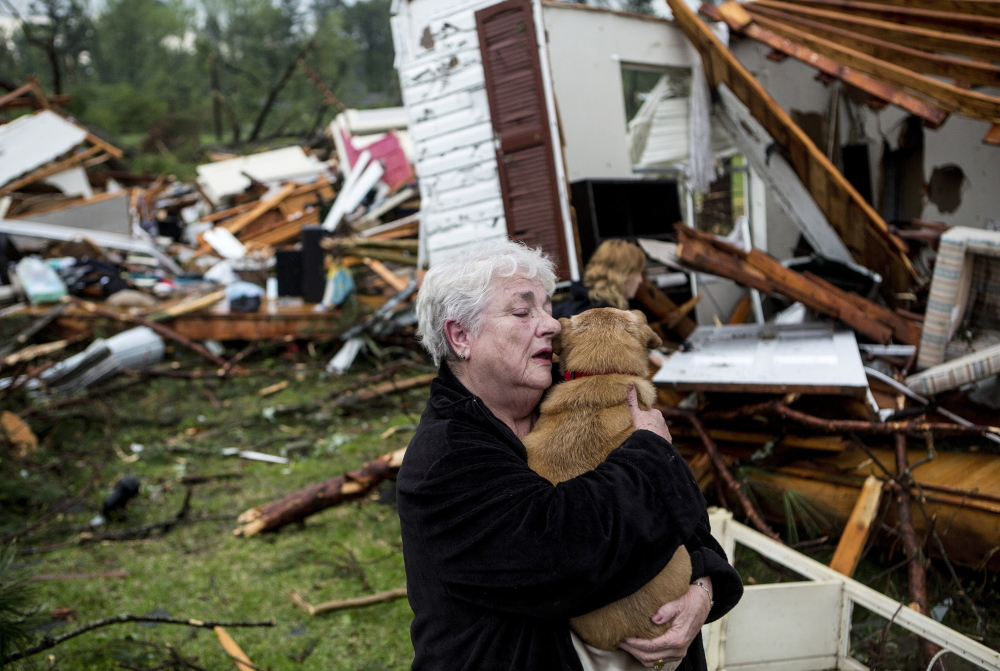Constance Lambert embraces her dog after finding it alive when returning to her destroyed home in Tupelo, Miss., Monday. Lambert was at an event away from her home when a tornado struck.