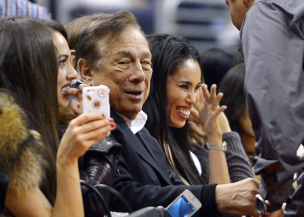 In this Oct. 25, 2013, photo Los Angeles Clippers owner Donald Sterling, center, and V. Stiviano, right, watch the Clippers play the Sacramento Kings in Los Angeles.
