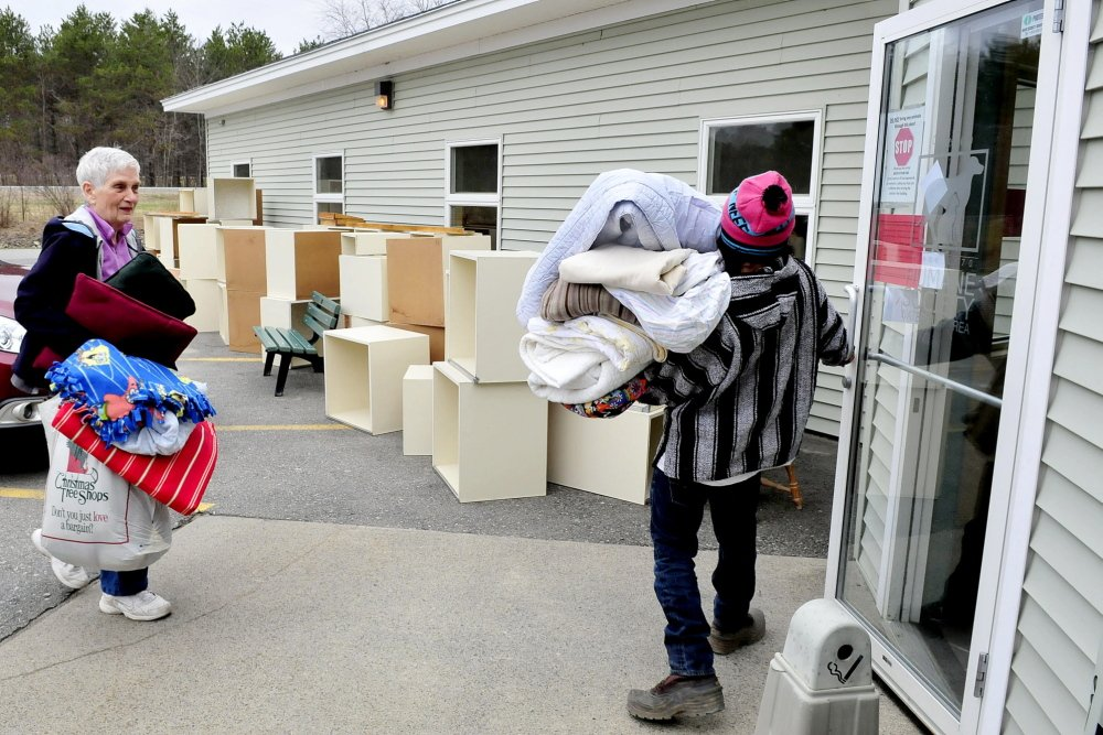 WELCOME DONATIONS: Humane Society Waterville Area employee Luis Mauser holds the door for Jane Bird, who donated bedding for animals at the shelter on Monday. In the background are boxes for cats stored outside and will be discarded because of a ringworm outbreak.